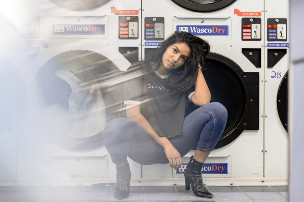 woman-sitting-in-front-of-washing-machine